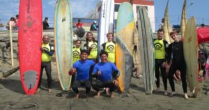 Group shot of surfers taking part in a lesson standing on the beach with their surf boards and instructors